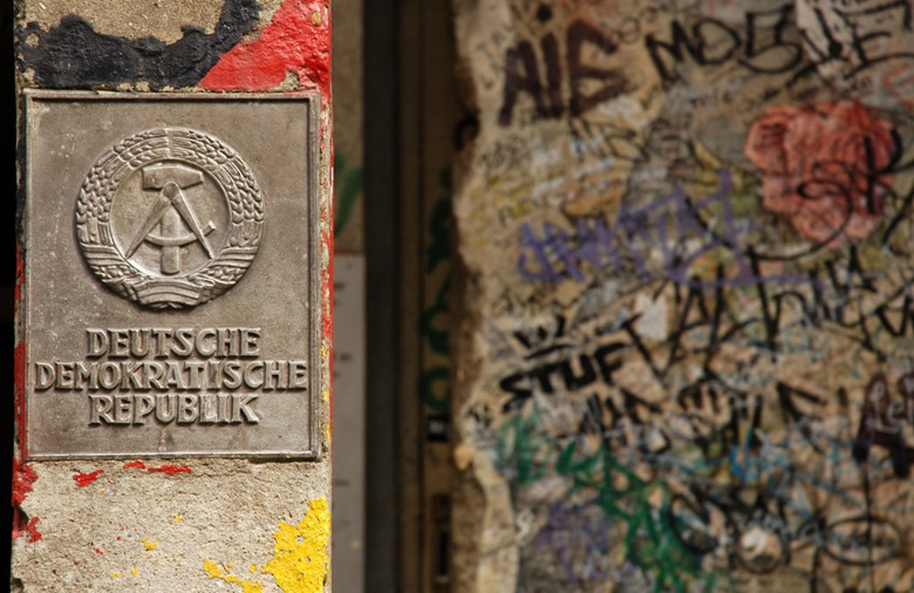 Stock Photo: 4409-49188 Germany. Berlin. The National Emblem of the German Democratic Republic. A hammer and a compass, surrounded by a ring of rye next to a section of the Berlin Wall.