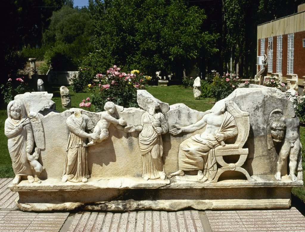 Stock Photo: 4409-54338 ARTE ROMANO. TURQUIA. SARCOFAGO ROMANO decorado con relieves donde se representa una escena familiar. Una esclava muestra al matrimonio romano su hijo pequeño. En ambos extremos de la cara del sarcófago, amorcillos. Museo de AFRODISIA DE CARIA.