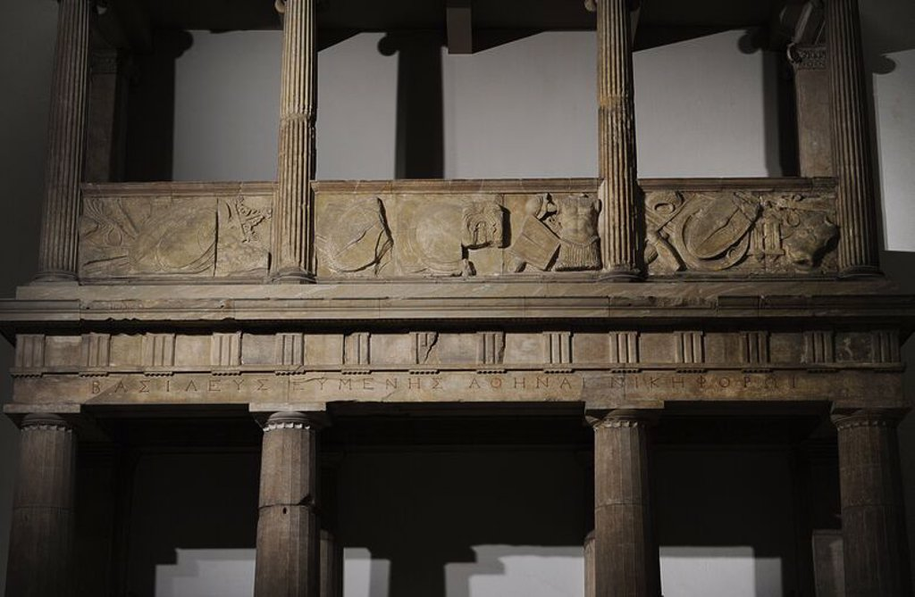 Propylaea of __the Sanctuary of Athena. 3rd - 2nd centuries BC. Architrave with the dedication from king Eumenes to Athena Nikephore. At the balcony, the weapons of the defeates Galates. Detail. Acropolis of Pergamum. Pergamon Museum. Berlin. Germany. : Stock Photo