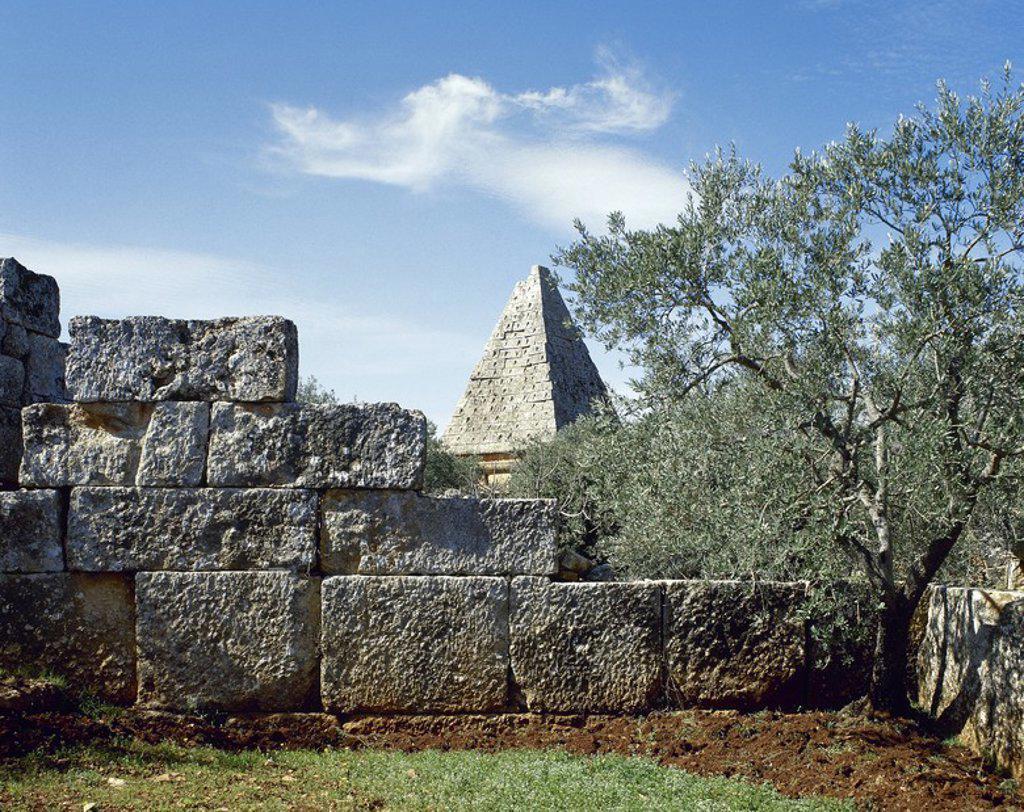 ARTE BIZANTINO. SIGLO V. SIRIA. BARA (AL-KAFR). Una de las Ciudades Muertas de los alrededores de Maarat al-Numan. En el siglo V, la ciudad era un importante centro religioso. Vista parcial de recinto arqueológico con un MAUSOLEO-PIRAMIDE al fondo. : Stock Photo