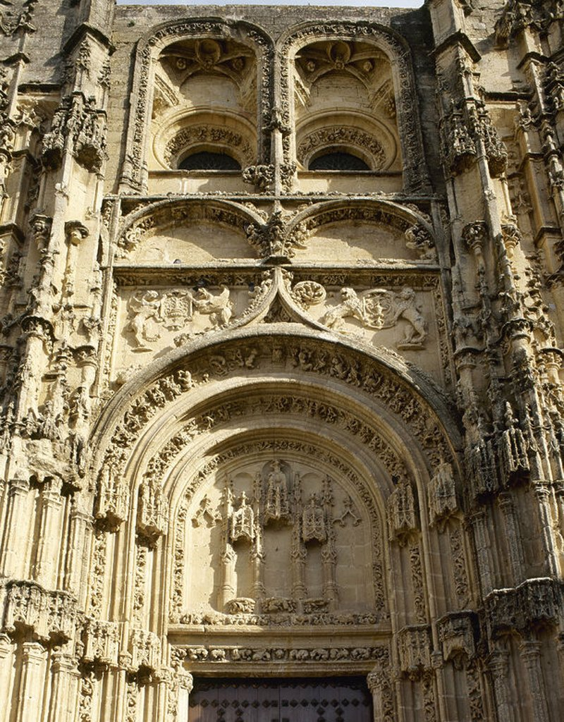 Stock Photo: 4409-64900 ARTE GOTICO-PLATERESCO. ESPAÑA. IGLESIA DE SANTA MARIA. Detalle de la FACHADA PRINCIPAL (inicios del s. XV). Presenta puerta adintelada bajo un triple arco de estilo florentino sobre el que se empinan dos leones que portan ánforas catedralicias. El conjunto está coronado por dos rosetones en ventanas ciegas. ARCOS DE LA FRONTERA. Provincia de Cádiz. Andalucía.