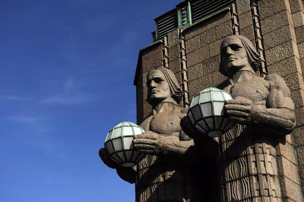 """FINLANDIA. HELSINKI. ESTACION CENTRAL DE TREN. Diseñado por Eliel Saarinen en 1914 en estilo Art Nouveau finlandés. Detalle de los de las cuatro estatuas que decoran la entrada sur de la estación. """"LOS DEMANDANTES DE LA LUZ (granito) """", obra del escultor finlandés EMIL WIKSTROM (1864-1943) . : Stock Photo"""