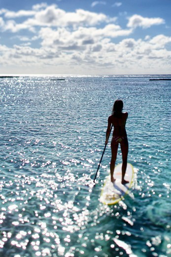 Stock Photo: 4411-6347 Young Woman Stand Up Paddling In Shimmering Light,Moorea, Tahiti, French Polynesia, South Pcific Ocean