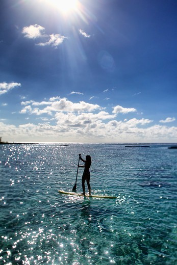 Stock Photo: 4411-6350 Young Woman Stand Up Paddling In Shimmering Light,Moorea, Tahiti, French Polynesia, South Pcific Ocean