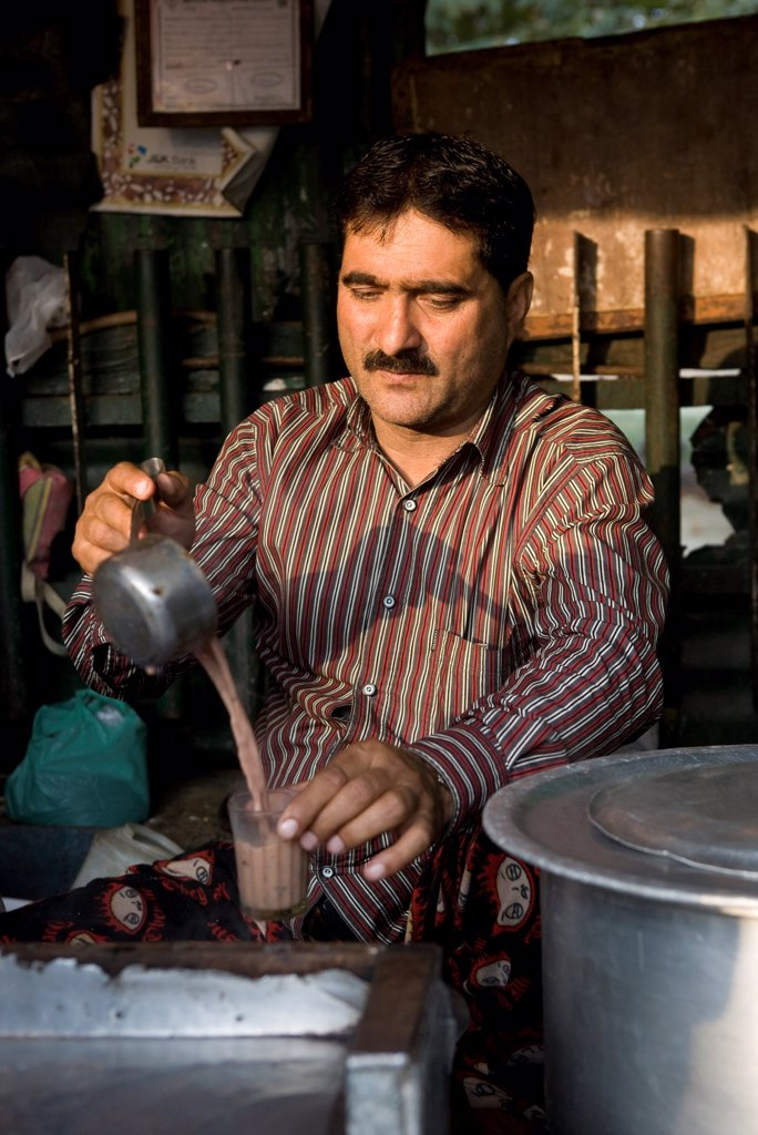 Men serve tea to the bus station in Srinagar India : Stock Photo