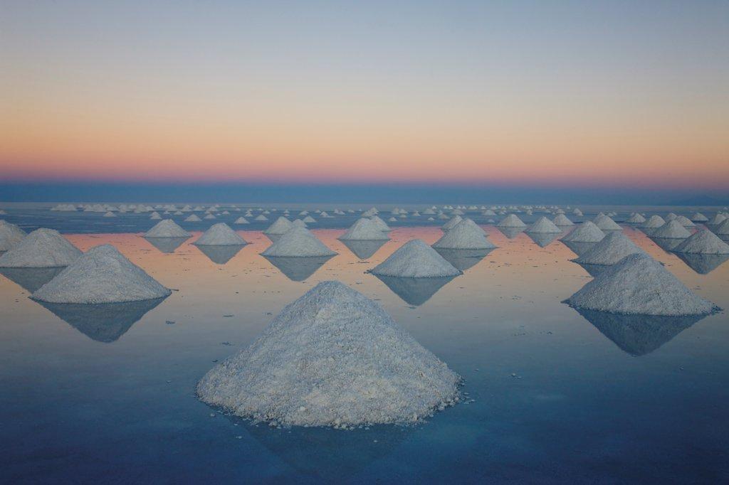 Conical mounds of salt on Salar de Uyuni at sunset Bolivia : Stock Photo