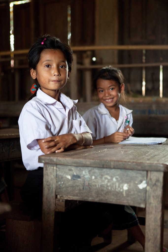 Girls behind their desks in a school in Laos : Stock Photo
