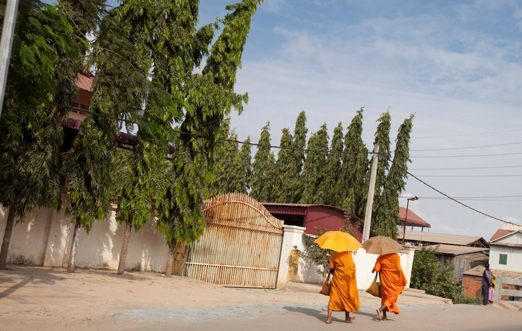 Monks walking down a street in the outskirts of Phnom Penh : Stock Photo