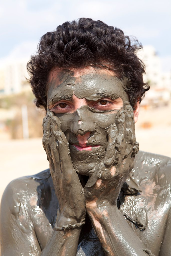 Stock Photo: 4413-200531 Tourist smearing mud on the banks of the Dead Sea Jordan