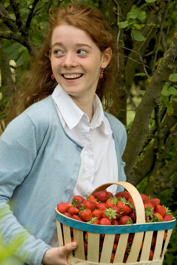 Portrait of a young girl with a basket of strawberries : Stock Photo