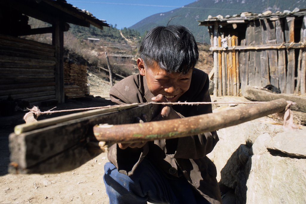 Stock Photo: 4413-2962 Yi child playing with his crossbow Yunnan China