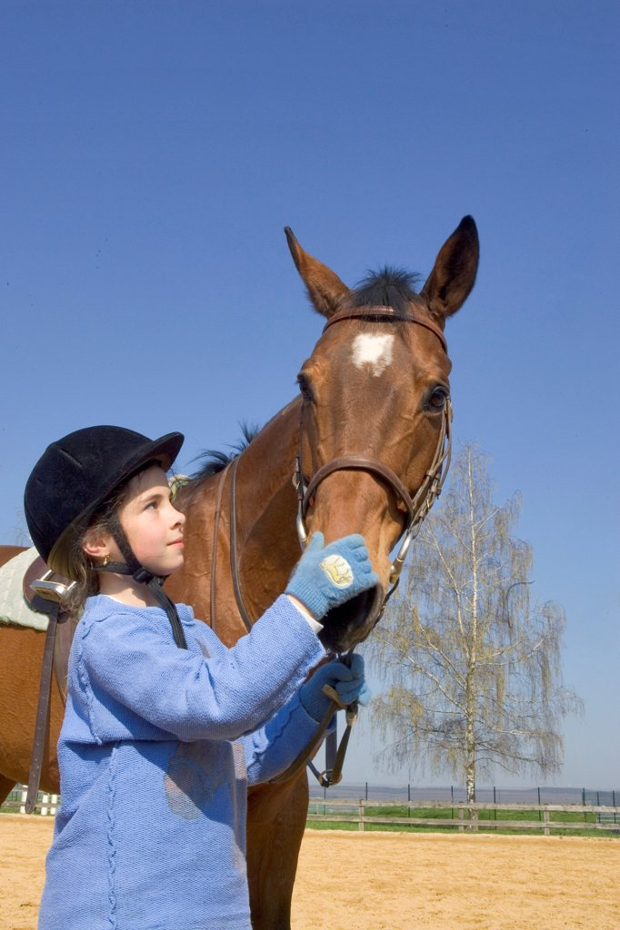 Young rider on the ground stroking her Horse's nostrils : Stock Photo