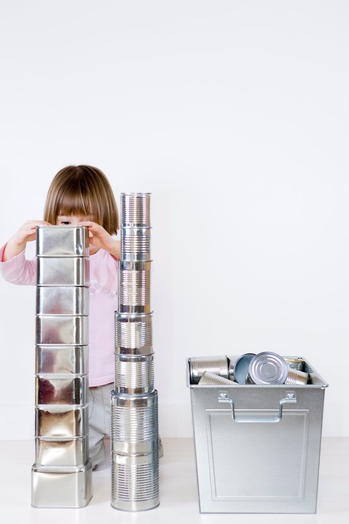 Stock Photo: 4413-41113 Girl playing to build a cans stack