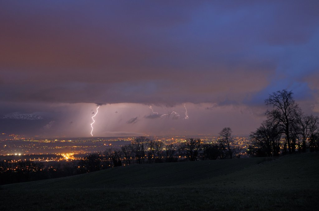 Lightning in a curtain of rain on the country of Gex France : Stock Photo