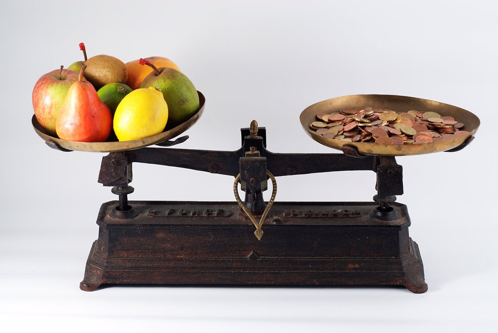 Former balance with fruit and coins : Stock Photo