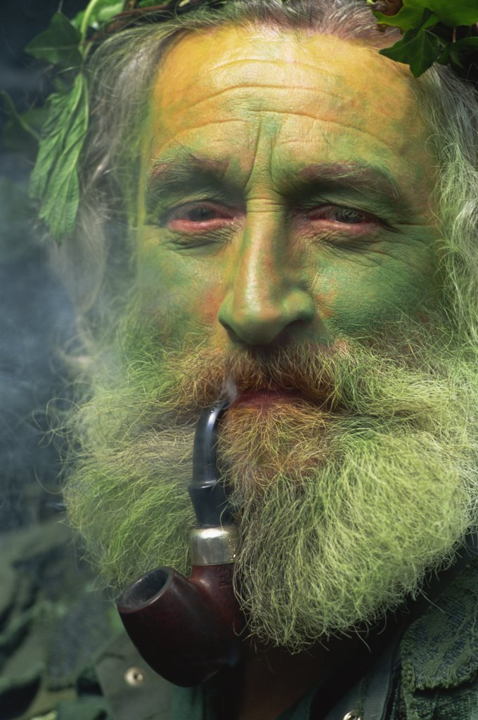 Stock Photo: 442-10633 Portrait of a Jack in the Green attendant smoking a pipe, Rochester, Kent, England
