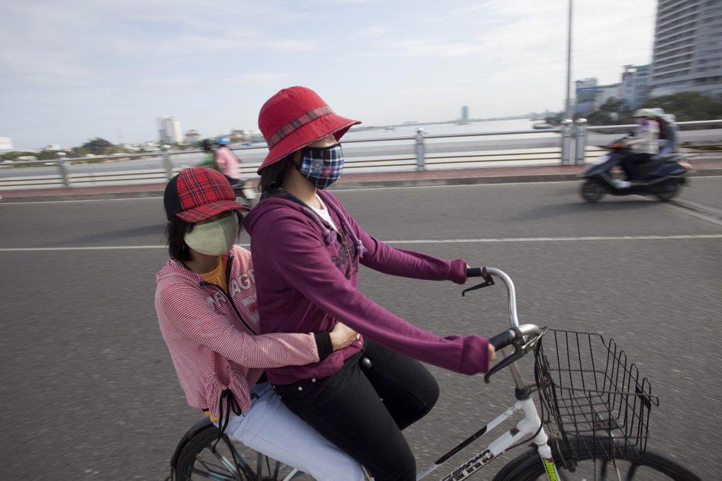 Two women riding a bicycle, Danang, Vietnam : Stock Photo