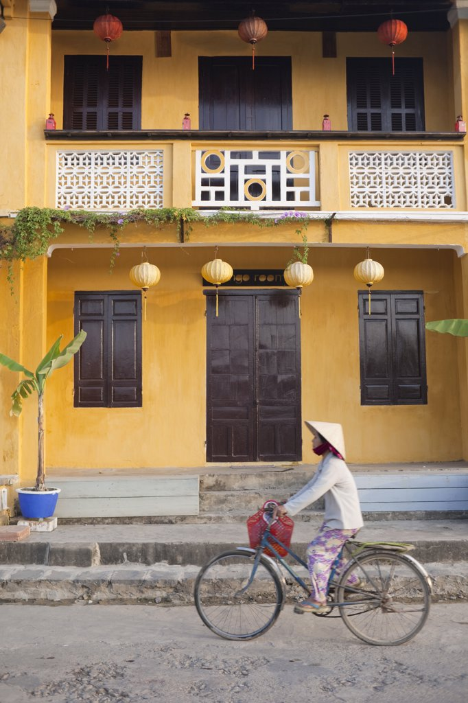 Stock Photo: 442-11215 Person riding a bicycle in front of a cafe, Hoi An, Vietnam
