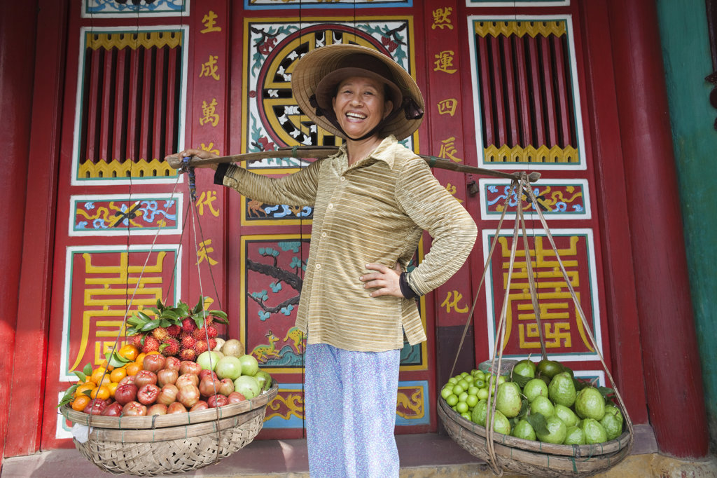 Female market vendor selling fruits, Hoi An, Vietnam : Stock Photo