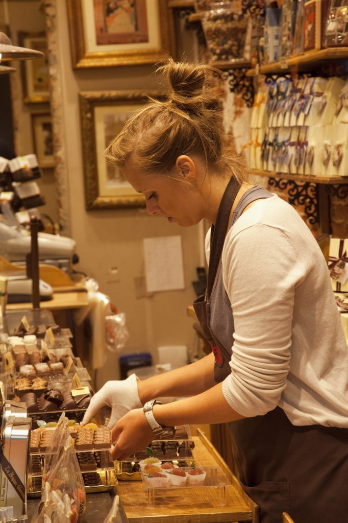 Belgium, Brussels, Chocolate shop sales girl : Stock Photo