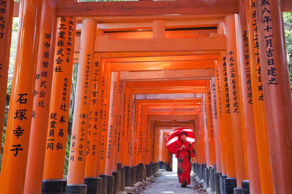 Stock Photo: 442-12531 Woman walking in the tunnel of a Torii gate, Fushimi Inari Shrine, Kyoto Prefecture, Kinki Region, Honshu, Japan