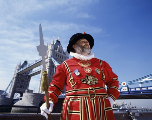 Stock Photo: 442-1746 Low angle view of a Beefeater standing with a bridge in the background, Tower Bridge, London, England