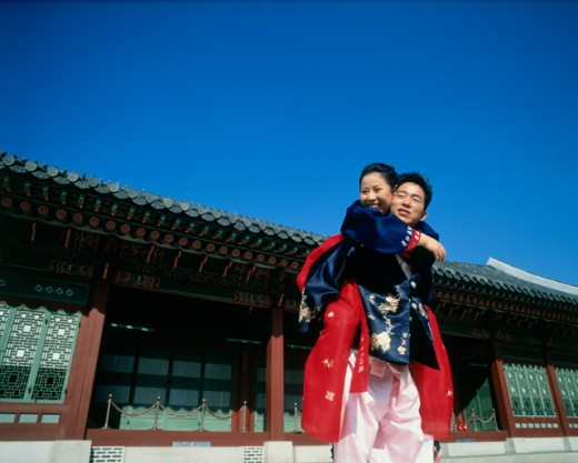 Stock Photo: 442-2837C Low angle view of a young woman riding piggyback on a young man, Kyongbok Palace, Seoul, South Korea