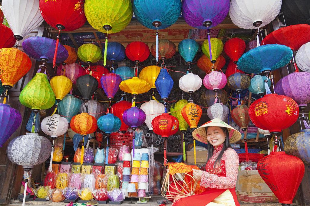 Teenage girl making paper lanterns at a market stall, Hoi An, Vietnam : Stock Photo