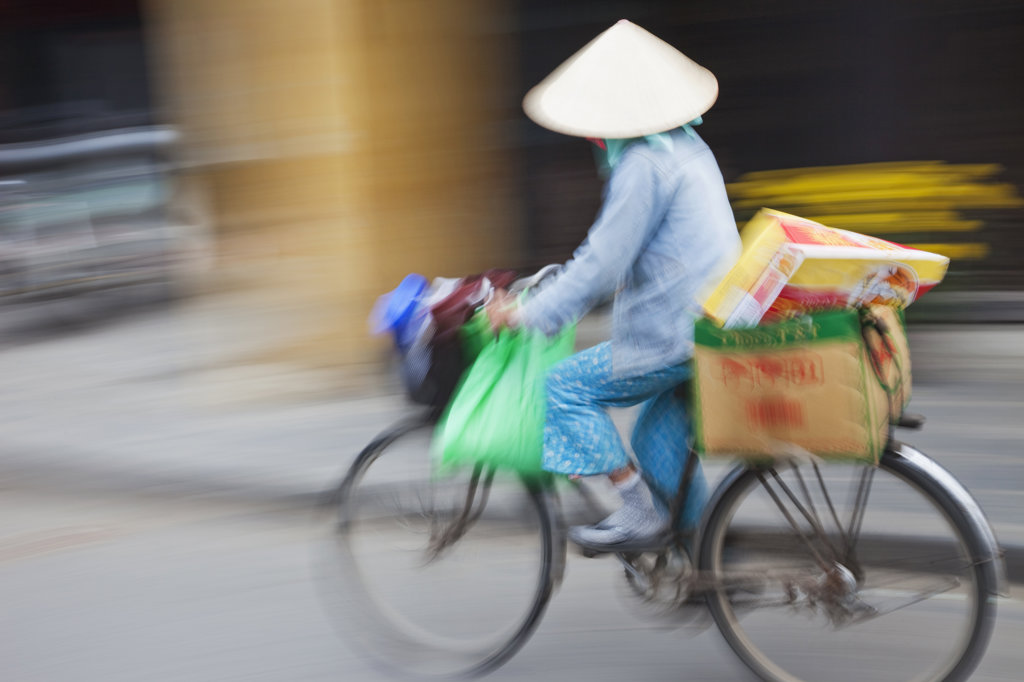 Female vendor on a bicycle in a street, Hoi An, Vietnam : Stock Photo