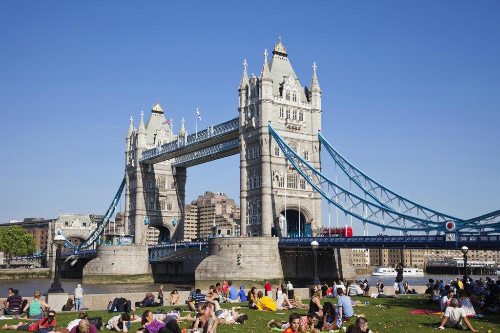 Tourists sitting near a bridge, Tower Bridge, Thames River, London, England : Stock Photo