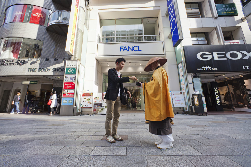 Monk receiving alms from a man, Ginza, Tokyo, Japan : Stock Photo