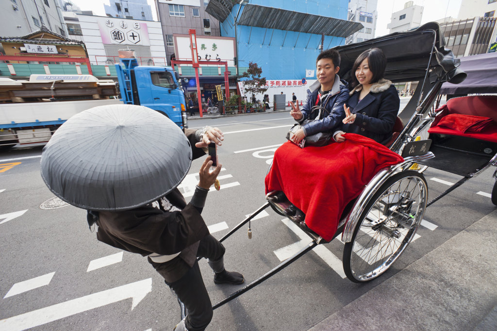 Rickshaw driver taking picture of a couple, Asakusa, Tokyo, Japan : Stock Photo