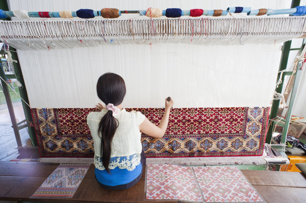 Woman weaving carpet in a loom, Thailand : Stock Photo
