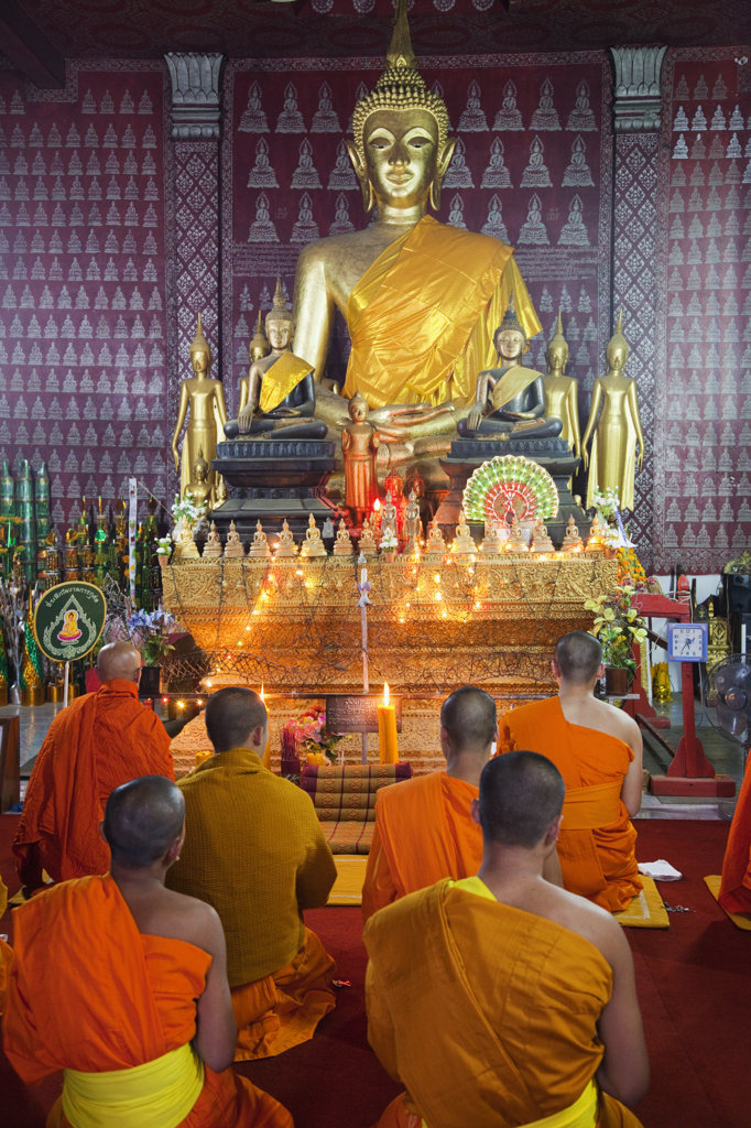 Stock Photo: 442-36972 Monks praying in the main prayer hall, Wat Phone Xai, Luang Phabang, Laos