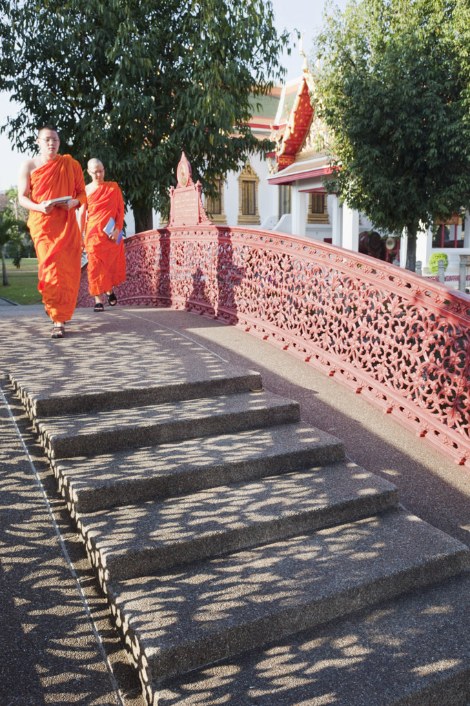 Stock Photo: 442-37014 Two monks Walking in the temple grounds Wat Benchamabophit (also known as the Marble Temple), Bangkok, Thailand