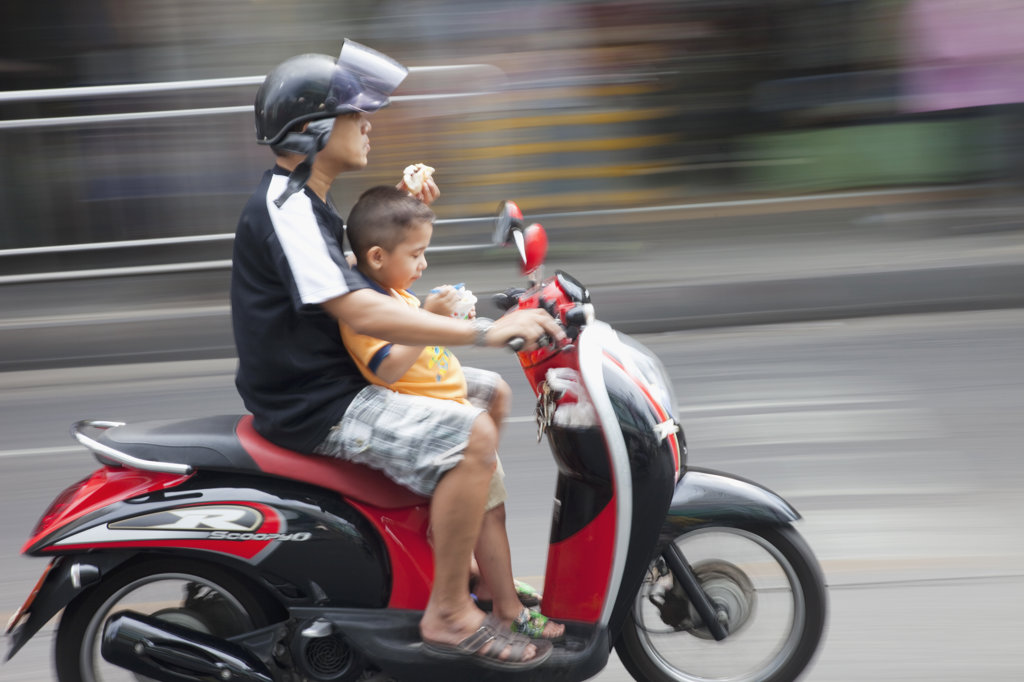 Stock Photo: 442-37055 Man riding motor cycle with his son on street, Bangkok, Thailand