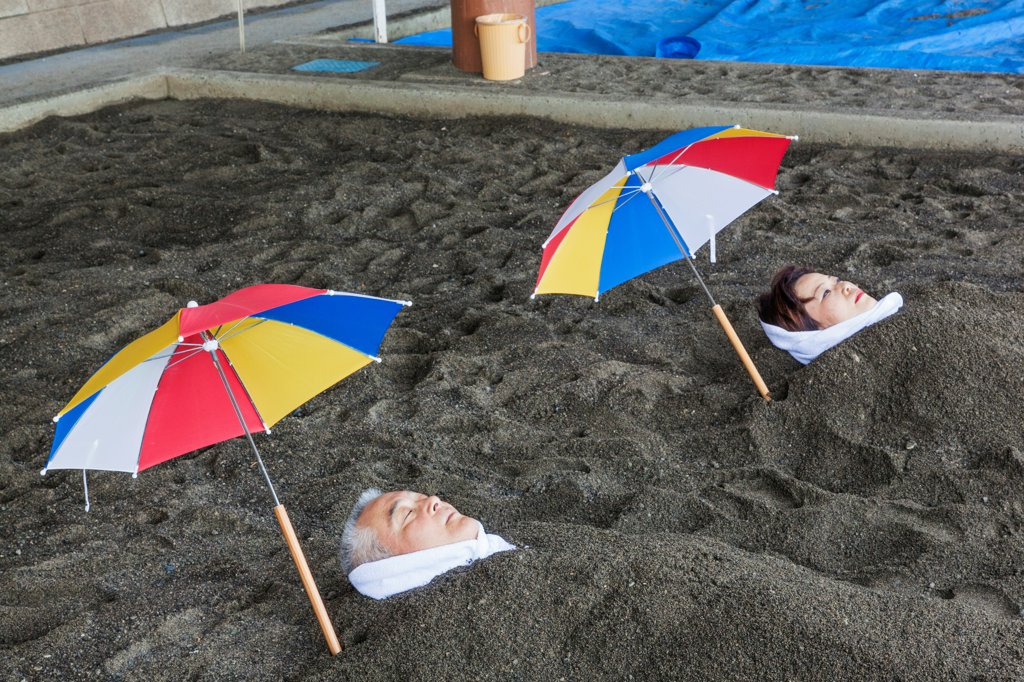 Japan, Kyushu, Kagoshima, Ibusuki, Thermal Sand Baths, Man and Woman Relaxing in Sand : Stock Photo