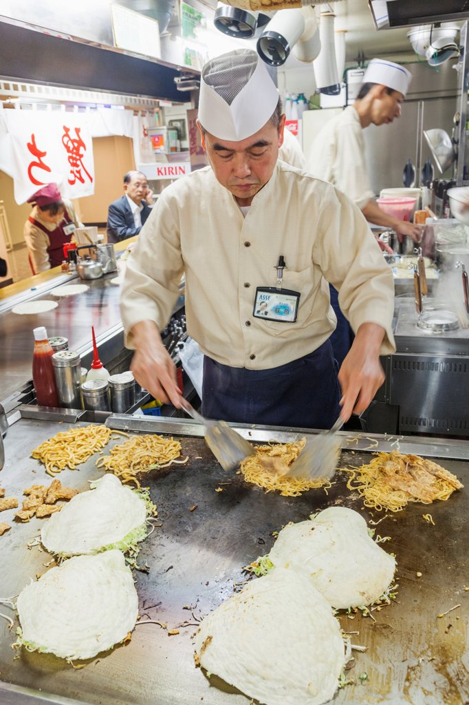 Japan, Kyushu, Hiroshima, Chef Cooking Okonomiyaki : Stock Photo
