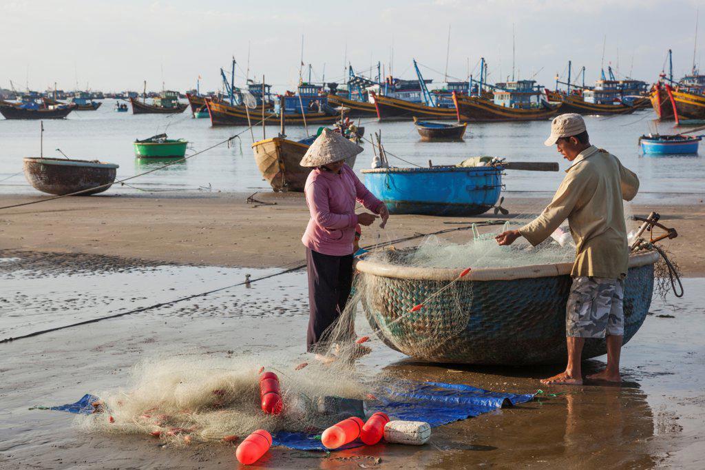 Stock Photo: 442-39024 Vietnam, Mui Ne, Mui Ne Beach, Fishermen with Coracle Fishing Boat