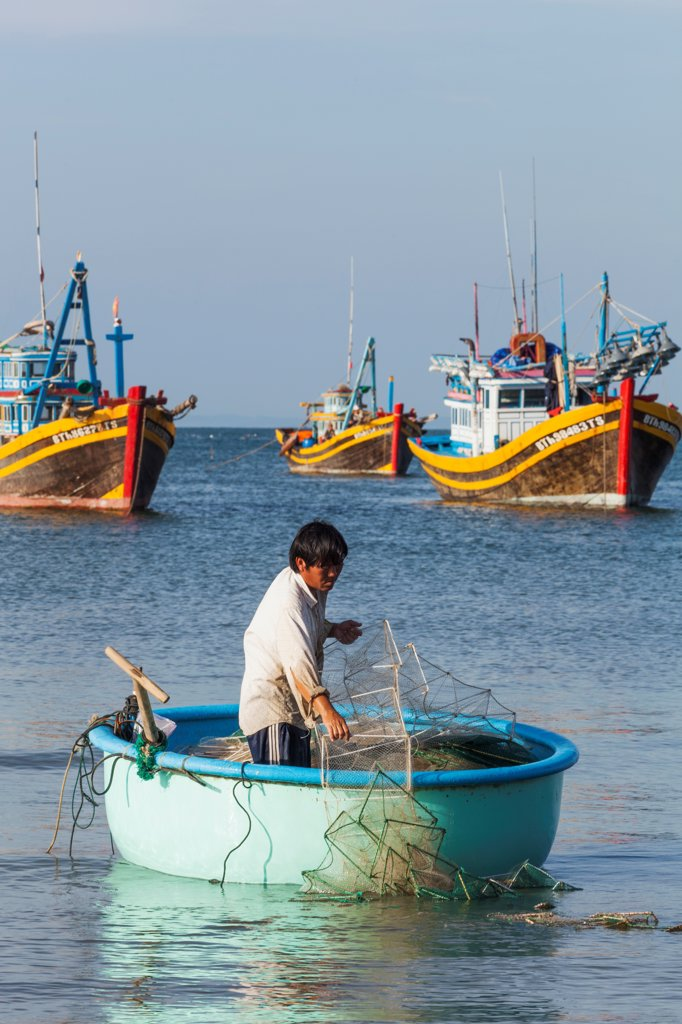 Stock Photo: 442-39030 Vietnam, Mui Ne, Mui Ne Beach, Fisherman in Coracle Fishing Boat