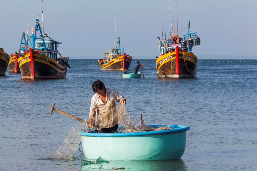 Vietnam, Mui Ne, Mui Ne Beach, Fisherman in Coracle Fishing Boat : Stock Photo