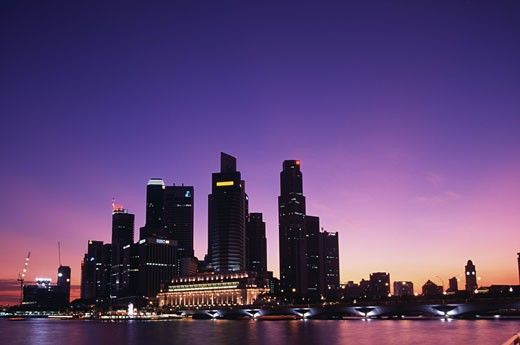 Skyscrapers lit up at night, Singapore : Stock Photo