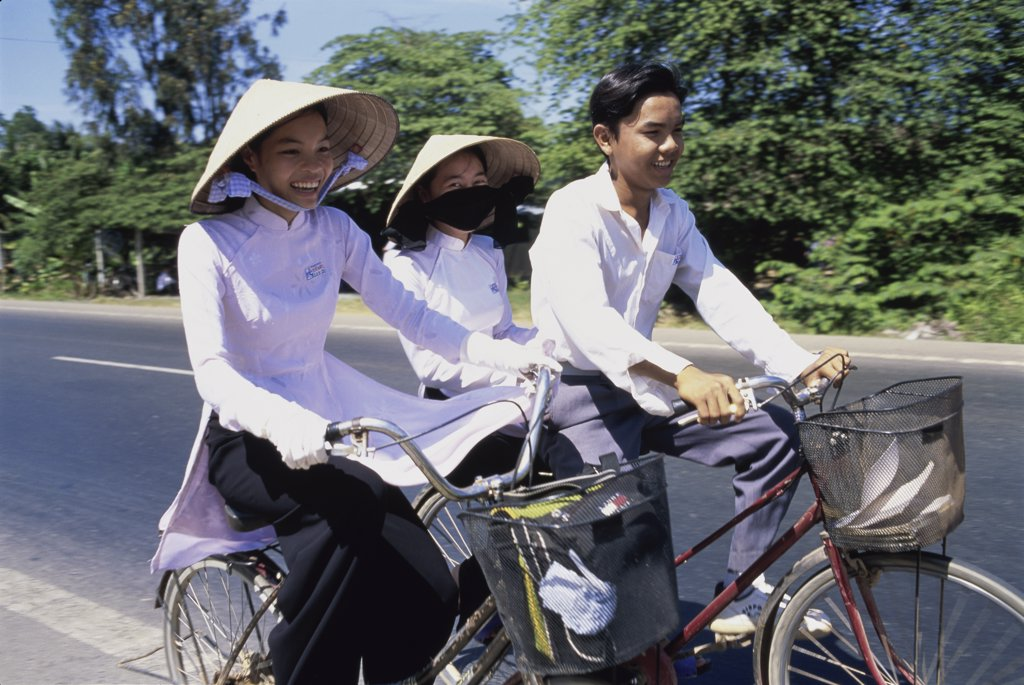 Three people cycling, Can Tho, Vietnam : Stock Photo