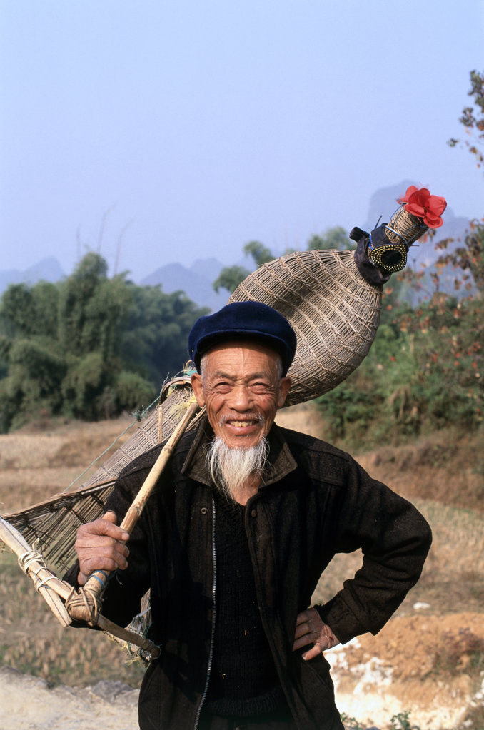 Portrait of a mature man holding fishing equipment, Yangshou, China : Stock Photo