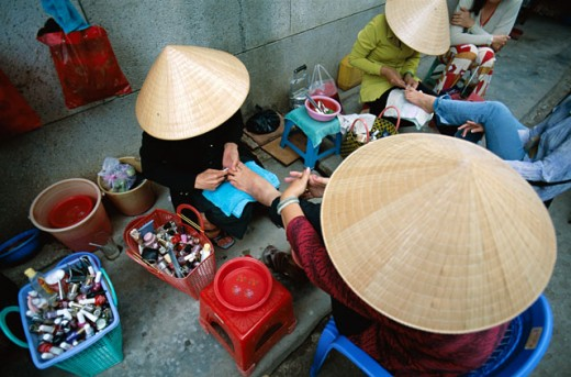 Stock Photo: 442-6234 High angle view of two women wearing traditional conical hats getting pedicures, Can Tho, Vietnam