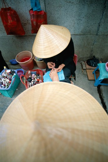 Stock Photo: 442-6235 High angle view of a woman wearing a traditional conical hat getting a pedicure, Can Tho, Vietnam