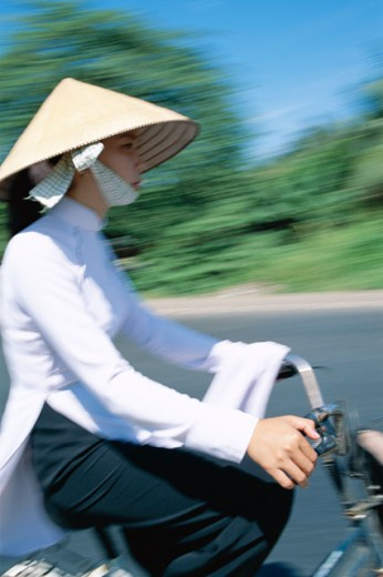 Stock Photo: 442-6238 Side profile of a teenage girl wearing a traditional conical hat cycling, Vietnam