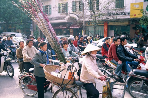 People on bicycles and motorcycles on a busy road in a market, Hanoi, Vietnam : Stock Photo