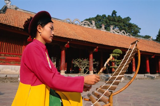 Side profile of a young woman playing a bamboo musical instrument, Temple of Literature, Hanoi, Vietnam : Stock Photo