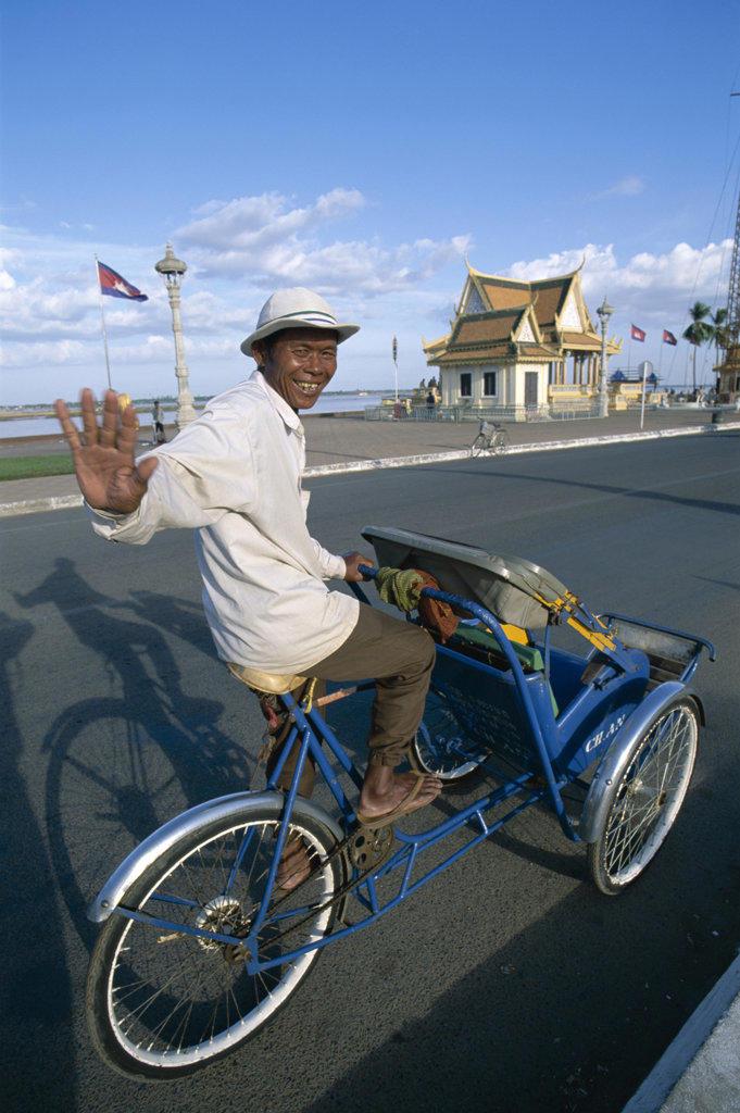 Stock Photo: 442-6392 Portrait of a rickshaw driver waving, Phnom Penh, Cambodia